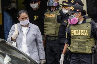 Peruvian politician Keiko Fujimori (L) wears a face mask -against the spread of the COVID-19 coronavirus- while leaving Santa Monica jail in Lima on May 04, 2020, following her release under bail after spending three months in pre-trial detention in a corruption case linked to Brazilian construction giant Odebrecht. (Photo by ERNESTO BENAVIDES / AFP)