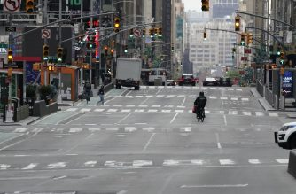 A man bikes down an empty Times Square in New York City on  May 6, 2020. - Authorities say conditions in New York -- the epicenter of the pandemic, with more than 19,000 confirmed or probable deaths -- are slowly improving, but that it's too soon to relax confinement measures. (Photo by TIMOTHY A. CLARY / AFP)