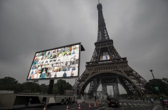The lettering 'Paris thanks those that are never thanked enough' and portraits of representatives of professional groups who were mobilized during the COVID-19 pandemic are displayed to pay tribute to them, on a giant screen in front of The Eiffel Tower in Paris on May 10, 2020, on the eve of France's easing of lockdown measures in place for 55 days to curb the spread of the pandemic, caused by the novel coronavirus. (Photo by Thomas SAMSON / AFP)