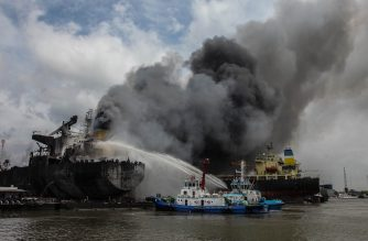 Fire fighters onboard a vessel try to extinguish a fire on a tanker ship docked in Belawan on May 11, 2020. (Photo by Ivan Damanik / AFP)