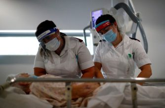 Radiologists Emma Parker and Gemma Ainsworth wearing protective face masks and visors comfort a patient before an X-ray in the X-ray department at the Royal Blackburn Teaching Hospital in Blackburn, north-west England on May 14, 2020, as national health service (NHS) staff in Britain fight the novel coronavirus COVID-19 pandemic. (Photo by HANNAH MCKAY / POOL / AFP)