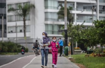 A woman walks with her daughter wearing face masks in a street in Lima on May 18, 2020. - Peruvian children and adolescents are able to go for short walks as of this Monday, after nine weeks of confinement in their homes due to measures taken to stop the spread of the novel Covid-19 coronavirus. (Photo by ERNESTO BENAVIDES / AFP)