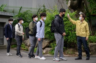 Students wearing facemasks amid concerns over the COVID-19 novel coronavirus undergo a temperature check as they arrive at Keongbok High School in Seoul on May 20, 2020. - Hundreds of thousands of South Korean students returned to classes as schools started reopening after more than a two-month delay over the coronavirus outbreak. (Photo by Ed JONES / AFP)