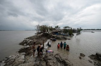 Volunteers and residents work to repair a damaged dam following the landfall of cyclone Amphan in Burigoalini on May 21, 2020. - At least 84 people died as the fiercest cyclone to hit parts of Bangladesh and eastern India this century sent trees flying and flattened houses, with millions crammed into shelters despite the risk of coronavirus. (Photo by Munir uz Zaman / AFP)