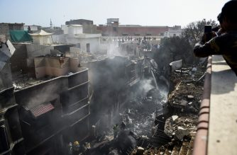 Rescue workers gather at the site after a Pakistan International Airlines aircraft crashed in a residential area in Karachi on May 22, 2020. - A Pakistani passenger plane with nearly 100 people on board crashed into a residential area of the southern city of Karachi on May 22. (Photo by Rizwan TABASSUM / AFP)