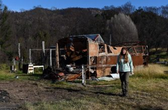 This picture taken on May 21, 2020 shows Anita Lawrence walking in front of a charred bus near to where she lives with her five children in a makeshift shelter months on from the devastating bushfires in Bemboka, a town on the south coast of New South Wales state. - Victims of Australia's catastrophic bushfires are still living in tents, garages and makeshift shelters months after the blazes ended, with efforts to rebuild their lives hampered by the coronavirus pandemic. (Photo by Saeed KHAN / AFP) / To go with AFP story Australia-fire-virus-climate, Focus by Andrew LEESON