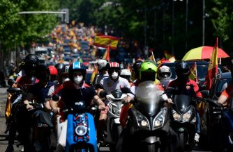 """Demonstrators take part in a """"caravan for Spain and its freedom"""" protest by far-right party Vox against the Spanish government in Madrid on May 23, 2020. - Spain, one of the most affected countries in the world by the novel coronavirus with 28,628 fatalities, has extended until June 6 the state of emergency which significantly limits the freedom of movement to fight the epidemic. The left-wing government's management of the crisis has drawn a barrage of criticism from righ-wing parties who have denounced its """"brutal confinement"""". (Photo by JAVIER SORIANO / AFP)"""