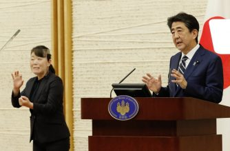 Japan's Prime Minister Shinzo Abe (R) speaks as a sign language interpreter wearing a face shield works (L) at a news conference in Tokyo on May 25, 2020. - Japan lifted a nationwide state of emergency over the coronavirus on May 25, gradually reopening the world's third-largest economy as government officials warned caution was still necessary to prevent another wave. (Photo by KIM KYUNG-HOON / POOL / AFP)