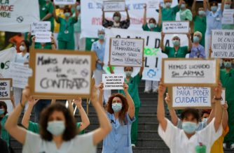 """A healthcare worker holds a sign reading """"14% of healthcare workers in Madrid are infected"""" during a protest calling for a reinforced healthcare system outside the Gregorio Maranon hospital in Madrid on May 25, 2020 as the country loosens a national lockdown that was put in place to fight the spread of the novel coronavirus. - Spain's government revised downward the country's death toll from the coronavirus by nearly 2,000, bringing the total number of deaths recorded to 26,834. (Photo by PIERRE-PHILIPPE MARCOU / AFP)"""
