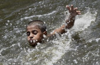 A boy cools himself off in a pond amid rising temperatures in New Delhi on May 26, 2020. (Photo by Money SHARMA / AFP)