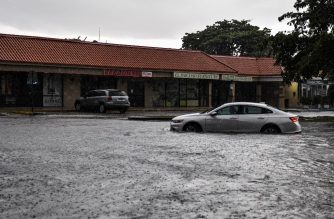 A woman drives through floodwater during heavy rainfall in Miami, on May 26, 2020. - Residents of South Florida couldn't enjoy the recent reopening of restaurants, businesses, and beaches after almost two months of quarantine due to the pandemic: three days in a row of heavy rains, which reached 6 inches on May 26, caused severe floods in Miami and other coastal cities affected by rising sea levels. (Photo by CHANDAN KHANNA / AFP)