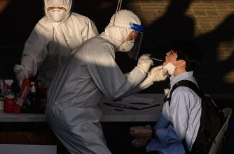 A health worker administers a swab at a temporary COVID-19 novel coronavirus testing centre in Bucheon, south of Seoul, on May 27, 2020. - South Korea reported its biggest jump in coronavirus infections in seven weeks on May 27, driven by a fresh cluster at an e-commerce warehouse on Seoul's outskirts, as millions more pupils went back to school. (Photo by Ed JONES / AFP)