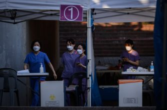 Health workers walk through a temporary COVID-19 novel coronavirus testing centre in Bucheon, south of Seoul, on May 27, 2020. - South Korea reported its biggest jump in coronavirus infections in seven weeks on May 27, driven by a fresh cluster at an e-commerce warehouse on Seoul's outskirts, as millions more pupils went back to school. (Photo by Ed JONES / AFP)