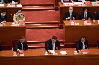 China's President Xi Jinping (C), Premier Li Keqiang (R) and Chairman of the Chinese People's Political Consultative Conference (CPPCC) Wang Yang (L) vote on a proposal to draft a Hong Kong security law during the closing session of the National People's Congress at the Great Hall of the People in Beijing on May 28, 2020. - China's rubber-stamp parliament endorsed plans on May 28 to impose a national security law on Hong Kong that critics say will destroy the city's autonomy. (Photo by NICOLAS ASFOURI / AFP)