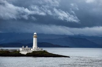 A lighthouse sits on a promontory as the ferry travels from the Isle of Oban to the Isle of Mull at first light on October 20, 2017. (Photo by ANDY BUCHANAN / AFP)