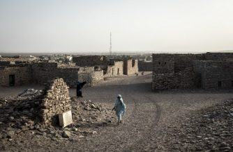 A woman walks through the Neolithic trading town of Tichitt on January 27, 2020. - Tichitt was once a thriving crossroads on the trans-Saharan caravan route and flourished between the 11th and 19th centuries. Merchants bearing gold, salt and cloth would stop to water their camels on the way to Timbuktu and settlements in the Niger river basin. (Photo by JOHN WESSELS / AFP)
