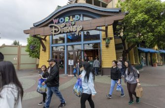 "People walk near the World of Disney store in Downtown Disney District shopping mall, which remains open on the first day of the closure of Disneyland and Disney California Adventure theme parks as fear of the spread of coronavirus continue, in Anaheim, California, on March 14, 2020. - The World Health Organization said March 13, 2020 it was not yet possible to say when the COVID-19 pandemic, which has killed more than 5,000 people worldwide, will peak. ""It's impossible for us to say when this will peak globally,"" Maria Van Kerkhove, who heads the WHO's emerging diseases unit, told a virtual press conference, adding that ""we hope that it is sooner rather than later"". (Photo by DAVID MCNEW / AFP)"