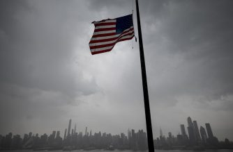 (FILES) In this file photo taken on April 21, 2020 a US flag  flies at half-mast in front of the Skyline of Manhattan of New York City seen from Weehawken, New Jersey. - US President Donald Trump tweeted on May 21, 2020 that he would order US flags lowered to half-staff for three days in honor of Americans who have died from the novel coronavirus. (Photo by Johannes EISELE / AFP)