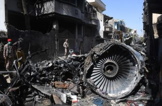Security personnel stand beside the wreckage of a plane at the site after a Pakistan International Airlines aircraft crashed in a residential area days before, in Karachi on May 24, 2020. - Ninety-seven people were killed and two survived when a passenger plane crashed into homes in Pakistan's southern city of Karachi on May 22. (Photo by Asif HASSAN / AFP)