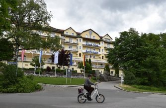A man cycles past the Hotel Sonnenbichl in Garmisch-Partenkirchen, southern Germany, on May 29, 2020. (Photo by Christof STACHE / AFP)