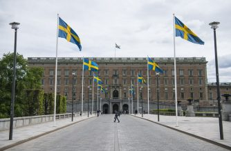 Swedish flags fly in front of the Royal Palace in Stockholm on May 29, 2020, amid the coronavirus COVID-19 pandemic. - Sweden's two biggest opposition parties called Friday for an independent commission to be appointed within weeks to probe the country's response to the new coronavirus. (Photo by Jonathan NACKSTRAND / AFP)