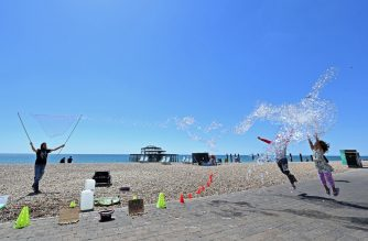 A man entertains children with bubble tricks in the sunshine on the beach in Brighton, on the south coast of England on May 31, 2020. - The UK government has set out a gradual easing of lockdown measures in England, with socially distanced groups of six friends and families allowed to meet in parks and gardens from June 1. (Photo by Glyn KIRK / AFP)