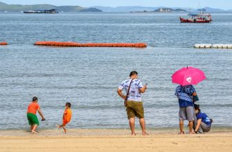 People enjoy the beach in Pattaya on June 1, 2020. - People flocked back to some of Thailand's famed sandy beaches June 1, keeping well apart but enjoying the outdoors, as authorities lifted coronavirus restrictions for the first time in more than two months. (Photo by Mladen ANTONOV / AFP)