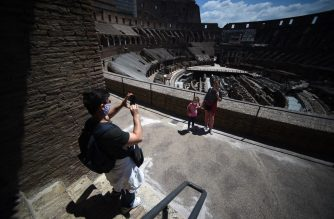 Visitors pose for a photo at the Colosseum monument which reopens to the public on June 1, 2020 in Rome, while the country eases its lockdown aimed at curbing the spread of the COVID-19 infection, caused by the novel coronavirus. - The Colosseum monument reopens on June 1, 2020 after having been closed since March 8, 2020, with adequate sanitary protection for staff and visitors, secure routes, compulsory reservations and modified schedules to avoid crowds at peak times. (Photo by Filippo MONTEFORTE / AFP)