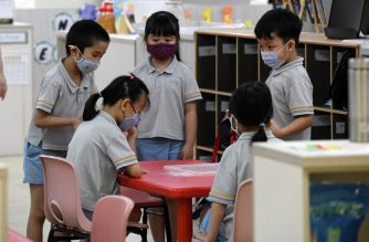 Children wearing face masks gather around a table inside their classroom as schools reopened in Singapore on June 2, 2020, as the city state eased its partial lockdown imposed to prevent the spread of COVID-19 in Singapore. (Photo by ROSLAN RAHMAN / AFP)