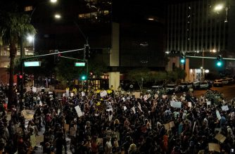 """People shout slogans and hold placards, on June 1, 2020, in downtown Las Vegas, as they take part in a """"Black lives matter"""" rally in response to the recent death of George Floyd, an unarmed black man who died while in police custody. - Thousands of National Guard troops patrolled major US cities after five consecutive nights of protests over racism and police brutality that boiled over into arson and looting, sending shock waves through the country. The death Monday of an unarmed black man, George Floyd, at the hands of police in Minneapolis ignited this latest wave of outrage in the US over law enforcement's repeated use of lethal force against African Americans -- this one like others before captured on cellphone video. (Photo by Bridget BENNETT / AFP)"""