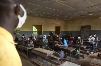 Malian students attend a lesson as the government decided to reopen the schools after two months of closure due to the spread of COVID-19 coronavirus, in Bamako on June 2, 2020. - All the students have been provided with masks to wear mandatorily and the lessons have been reorganised in order to have a maximum number of 25 students per classroom. (Photo by MICHELE CATTANI / AFP)