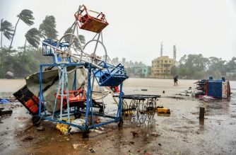 A man holding an umbrella walks past a small damaged ferris wheel and shacks at the beach in Alibag town of Raigad district, following cyclone Nisarga landfall in India's western coast. - Coronavirus-hit Mumbai appeared to escape the worst of Cyclone Nisarga on June 3 as the first severe storm to threaten India's financial capital in more than 70 years left it largely unscathed after ripping roofs off buildings in nearby coastal towns. (Photo by STR / AFP)