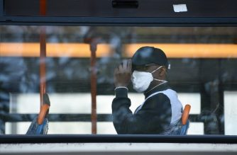 A man wears a protective face mask on a bus in central Manchester on June 5, 2020, as lockdown measures are eased during the novel coronavirus COVID-19 pandemic. - Face coverings will soon be compulsory for people wanting to travel on public transport in England to limit the spread of coronavirus. (Photo by Oli SCARFF / AFP)