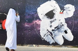 (FILES) In this file photo taken on September 25, 2019 a man takes a picture of an illustration depicting an astronaut with the Emirati national flag outside Mohammed Bin Rashid Space Centre (MBRSC) in Dubai. - The first Arab space mission to Mars, set for launch next month to study the Red Planet's atmosphere, is designed to inspire the region's youth and pave the way for scientific breakthroughs, officials said on June 9, 2020. (Photo by KARIM  SAHIB / AFP)