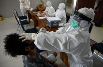 A medical staff member takes a swab sample from a man to test for the COVID-19 coronavirus in Denpasar on Indonesia's resort island of Bali on June 10, 2020. (Photo by SONNY TUMBELAKA / AFP)