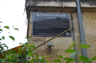 "A picture shows a  street plaque on the rue David Gradis in Bordeaux, on June 11, 2020, set up as part of new explanatory versions of street plaques bearing the names of city historical figures who took part in slave trade. - Bordeaux has set up five new versions of street plaques as part of an ""education of remembrance"" approach to deal with the city's slave trading past. (Photo by NICOLAS TUCAT / AFP)"