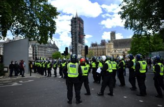 Police officers stand guard as members of far right groups gathered to guard statues in Parliament Square in central London on June 13, 2020, in the aftermath of the death of unarmed black man George Floyd in police custody in the US. - Police in London have urged people planning to attend anti-racism and counter protests on Saturday not to turn out, citing government regulations banning gatherings during the coronavirus pandemic. (Photo by Ben STANSALL / AFP)