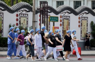 Medical personnel wearing face masks arrive at a swab testing facility to test people who live near or who have visited the Xinfadi Market, a wholesale food market where a new COVID-19 coronavirus cluster has emerged, in Beijing on June 16, 2020. - China reported another 27 domestically transmitted coronavirus cases in Beijing, where a fresh cluster linked to a wholesale food market has sparked WHO concern and prompted a huge trace-and-test programme. (Photo by Noel Celis / AFP)