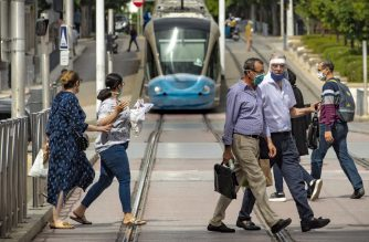People cross the street as a tram bearing a face protective mask to spread awareness on preventing the spread of coronavirus, arrives in the center of the Moroccan capital Rabat on June 16, 2020. (Photo by FADEL SENNA / AFP)