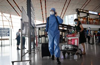 A man wearing a protective suit uses his phone at Beijing's international airport on June 17, 2020. - Beijing's airports cancelled more than 1,200 flights and schools in the Chinese capital were closed again on June 17 as authorities rushed to contain a new coronavirus outbreak linked to a wholesale food market. (Photo by STR / AFP)