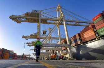 """An employee wearing a face mask against the coronavirus, is pictured at the port of Jebel Ali, operated by the Dubai-based giant ports operator DP World, in the southern outskirts of the Gulf emirate of Dubai, on June 18, 2020. - The chairman of Dubai-based giant ports operator DP World said it is """"preparing for the worst"""" with the full impact of coronavirus to hit in coming months, as global trade suffers its worst blow since World War II. The firm and its subsidiaries are a major source of cash for the emirate's economy, one of the most diversified in the oil-rich Gulf but mired in a long malaise. (Photo by KARIM SAHIB / AFP)"""