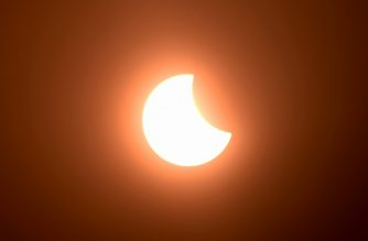 The moon partially covers the sun during an annular solar eclipse as seen from Phnom Penh on June 21, 2020. (Photo by TANG CHHIN Sothy / AFP)