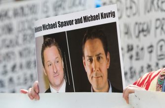 (FILES) In this file photo taken on May 8, 2019, Turnisa Matsedik-Qira, of the Vancouver Uyghur Association, demonstrates against China's treatment of Uighurs while holding a photo of detained Canadians Michael Spavor (L) and Michael Kovrig outside a court appearance for Huawei Chief Financial Officer, Meng Wanzhou at the British Columbia Supreme Court in Vancouver. - US Secretary of State Mike Pompeo on June 22, 2020 demanded that China free two Canadians who were charged with spying following a row involving all three nations. (Photo by Jason Redmond / AFP)