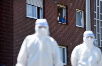 Men look on from a window to personell of a mobile testing unit of the German Red Cross and the German army (Bundeswehr), prior of testing the employees of the abatoir Toennies, at their residential homes in Verl, western Germany on June 23, 2020, amid the novel coronavirus pandemic. - German authorities ordered a new lockdown for the entire district of Guetersloh -- the first since easing coronavirus restrictions and a major setback for hopes of a swift return to normality. The lockdown would affect 360,000 people and would stay in place until at least June 30. (Photo by Ina FASSBENDER / AFP)