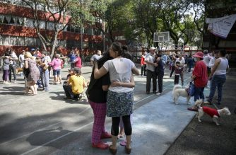People remain outside buildings in Mexico City during a quake on June 23, 2020 amid the COVID-19 novel coronavirus pandemic. - A 7.1 magnitude quake was registered Tuesday in the south of Mexico, according to the Mexican National Seismological Service. (Photo by Alfredo ESTRELLA / AFP)