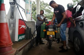 (FILES) In this file photo taken on January 11, 2019 A petrol attendant serves a motorcyclist with two jerry cans attached to his motorbike at a fuel station, on January 11, 2019 in Harare. - Zimbabwe on June 24, 2020 announced a sharp rise in the price of fuel following the launch of a forex auction system which eroded the value of the local currency. (Photo by Jekesai NJIKIZANA / AFP)