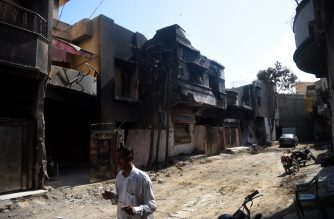 A msn walks pasthouses damaged during last month Pakistan International Airlines (PIA) plane crash, in Karachi on June 24, 2020. - A plane crash which killed 97 people in Pakistan last month was because of human error by the pilot and air traffic control, according to an initial report into the disaster released on June 24. (Photo by Rizwan TABASSUM / AFP)