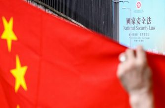 A billboard (top R) referring to the incoming National Security Law is seen beyond a Chinese national flag being held up by a pro-China activist during a rally outside the US Consulate General in Hong Kong on June 26, 2020, a day after the US Senate unanimously approved a bill that would lay out sanctions on Chinese officials who undermine Hong Kong's autonomy as Beijing pushes forward with a controversial security law. (Photo by Anthony WALLACE / AFP)
