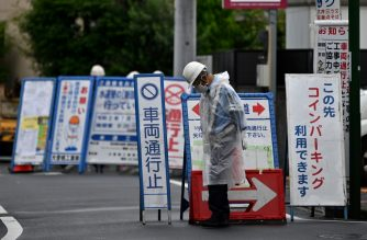 A security guard monitors a street next to a construction site in Tokyo on June 30, 2020. - Japan's unemployment rate rose to 2.9 percent in May, official data showed Tuesday, the third consecutive monthly rise as the coronavirus pandemic takes its toll on the world's number-three economy. (Photo by CHARLY TRIBALLEAU / AFP)