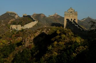 This photo taken on October 20 shows the sun setting over the autumn colours of a section of the Great Wall of China at Jinshanling, Hebei Province. The wall which is a series of fortifications made of stone, brick and rammed earth was subject to a recent archaeological survey that found its total length to be 21,196 km or 13,171 miles.        AFP PHOTO/Mark RALSTON (Photo by Mark RALSTON and - / AFP)